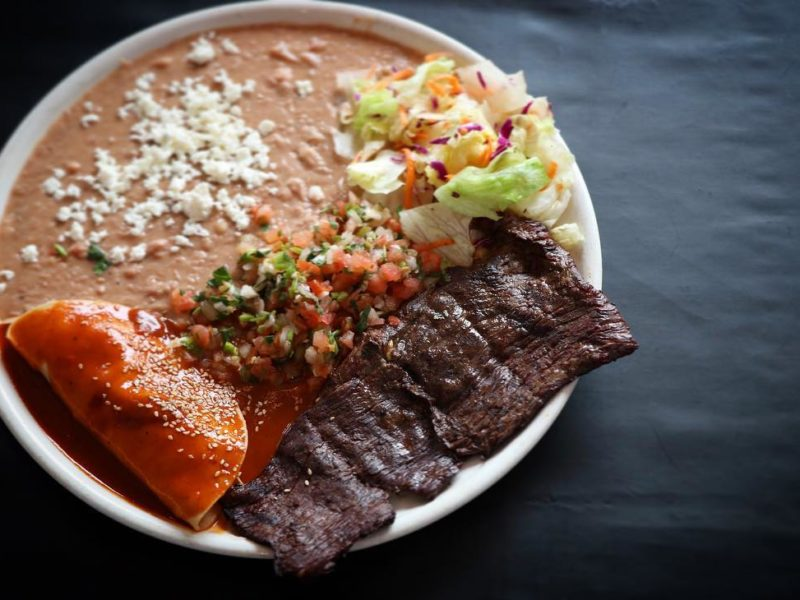 "Steak a La Tampiquena: Grilled skirt steak garnished with a chicken ""mole"" sauce enchilada and refried beans, served with fresh salad."