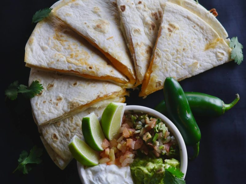 Cheese Quesadilla with a side dish with jalapenos.