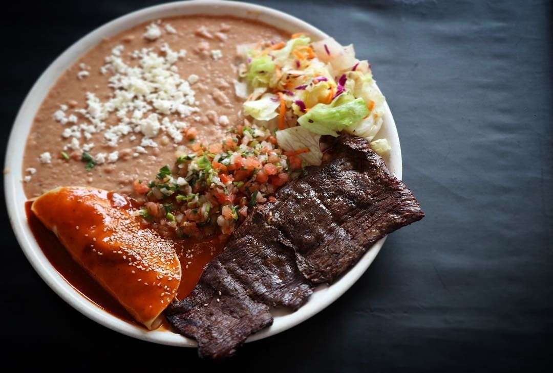 """Steak a La Tampiquena: Grilled skirt steak garnished with a chicken """"mole"""" sauce enchilada and refried beans, served with fresh salad."""