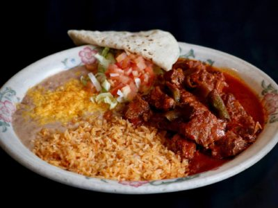 Chile Colorado: Beef simmered until very tender in a red sauce, tomatoes, onions, mild peppers and spices served with rice and beans.