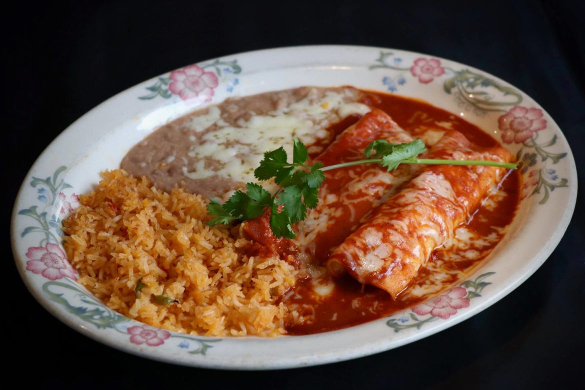 """Veggie enchiladas: Two corn tortillas stuffed with mushrooms, carrots, celery and peas topped with our original carrot pure and """"Ranchero"""" cheese served with rice and beans."""