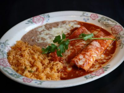 """Mole Enchiladas: Two tortillas, filled with you choice of meat topped with sweet """"Mole"""" sauce and Jack cheese served with rice and beans."""