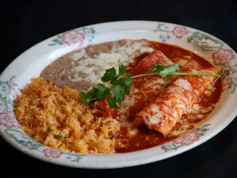 "Mole Enchiladas: Two tortillas, filled with you choice of meat topped with sweet ""Mole"" sauce and Jack cheese served with rice and beans."